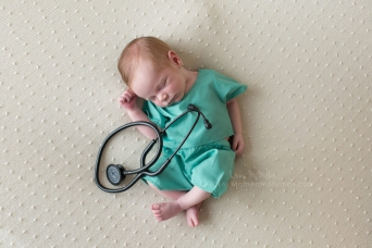 newborn baby dressed in hospital scrubs with stethiscope